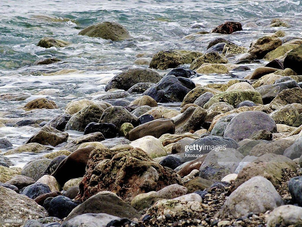 Onda del mar de la playa de arena y piedras exposición larga : Foto de stock
