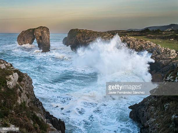 sea waves breaking on the cliff castro of gulls in llanes, asturias, spain. - llanes fotografías e imágenes de stock