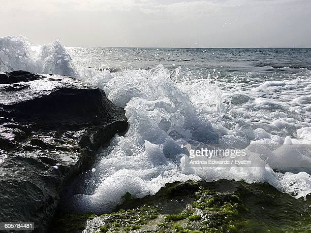 Sea Waves Rushing On Rock Formations Against Sky
