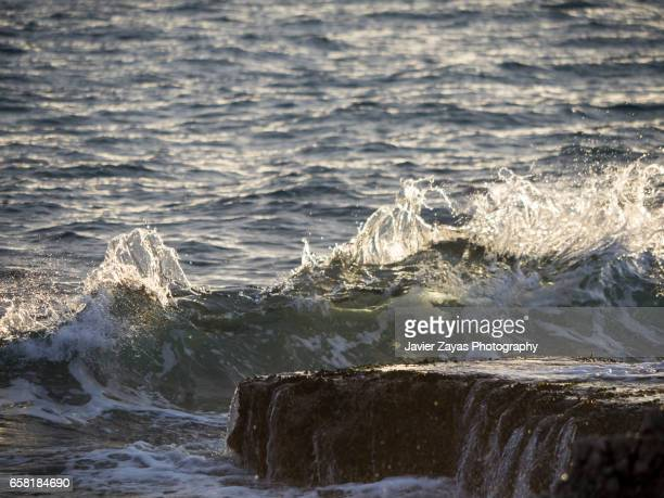 sea waves splashing on rock - mojado stock pictures, royalty-free photos & images