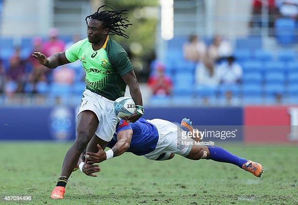 Seabelo Senatla of South Africa is tackled during the 2014 Gold Coast Sevens Cup semi-final match between South Africa and Samoa at Cbus Super...