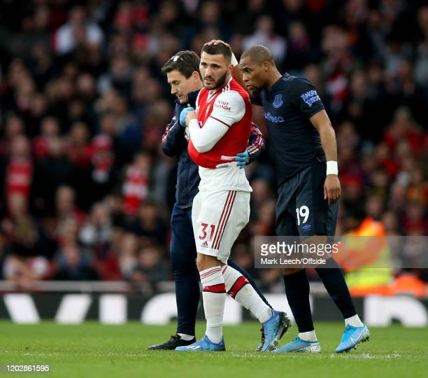Sead Kolasinac of Arsenal departs the pitch with an injury sustained in a collision with Djibril Sidibe of Everton during the Premier League match...