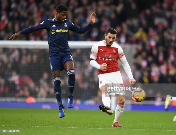 Sead Kolasinac of Arsenal passes the ball under pressure from Ryan Sessegnon of Fulham during the Premier League match between Arsenal FC and Fulham...