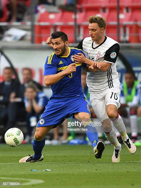 Sead Kolasinac of Bosnia and Herzegovina and Christian Eriksen of Denmark compete for the ball during the international friendly match between Bosnia...