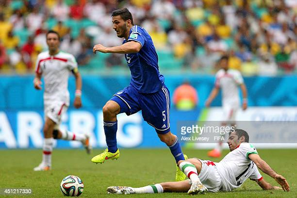 Sead Kolasinac of Bosnia and Herzegovina is tackled by Pejman Montazeri of Iran during the 2014 FIFA World Cup Brazil Group F match between...