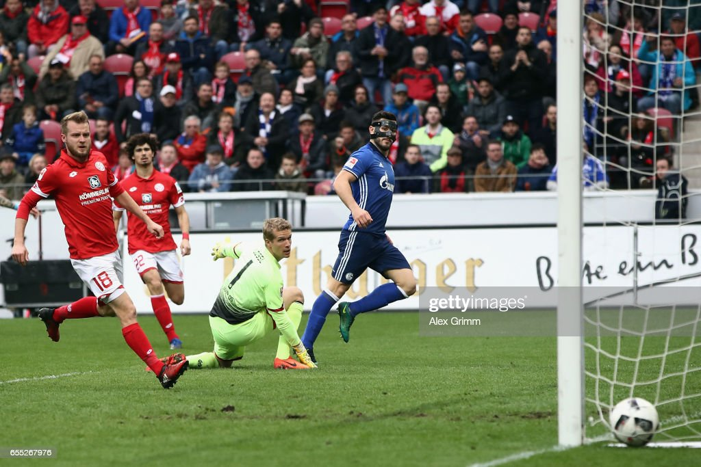 Sead Kolasinac of Schalke scores his team's first goal past goalkeeper Jonas Loessl and Daniel Brosinski of Mainz during the Bundesliga match between 1. FSV Mainz 05 and FC Schalke 04 at Opel Arena on March 19, 2017 in Mainz, Germany.