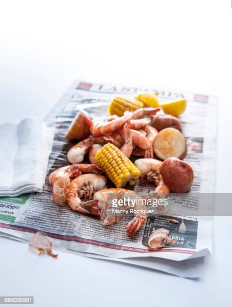 seafood boil on newspaper - shrimp seafood stock pictures, royalty-free photos & images