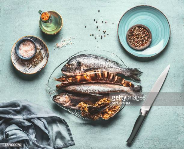 seafood cooking. fishes and crustaceans on kitchen table - aquaculture stock pictures, royalty-free photos & images