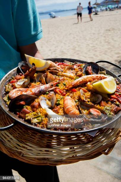 seafood paella on beach - paella stock photos and pictures