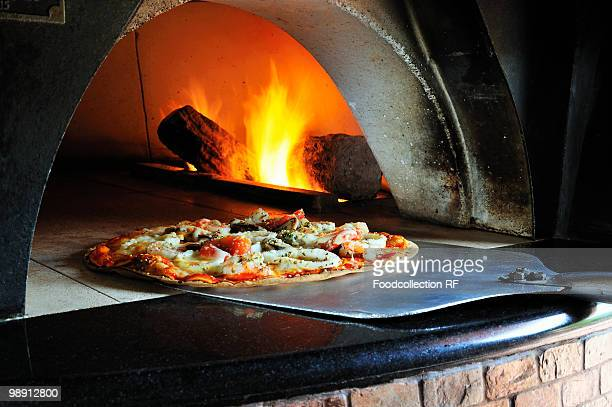 seafood pizza in stone oven - pizza oven stock photos and pictures