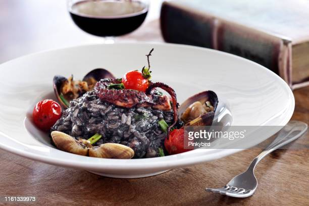 seafood risotto, paella from black rice with seafood,black risotto with octopus - black rice stock pictures, royalty-free photos & images
