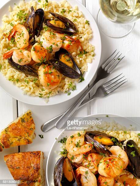 seafood risotto with fresh parsley and focaccia bread - crucifers stock pictures, royalty-free photos & images