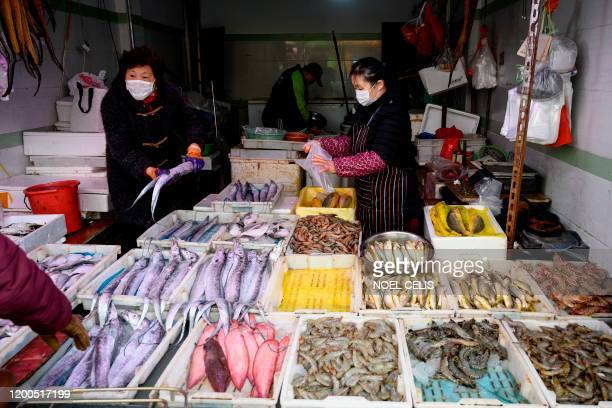 Seafood vendor wearing a face mask talks to a customer at a wet market in Shanghai on February 13, 2020. - China's official death toll and infection...