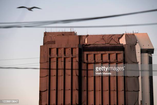 Seagull flies past protective netting draped on a tower illuminated at dusk as demolition continues at Trump Plaza Hotel & Casino, once one of the...
