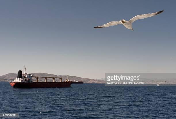 Seagulls fly over the sea on July 5 2015 in Aegina AFP PHOTO / IAKOVOS HATZISTAVROU