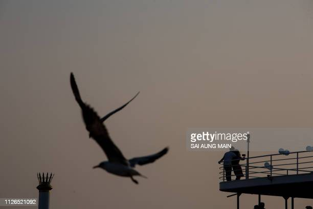 Seagulls fly while a couple takes a selfie during sunset while riding a ferry in Yangon River in Yangon on February 21, 2019.