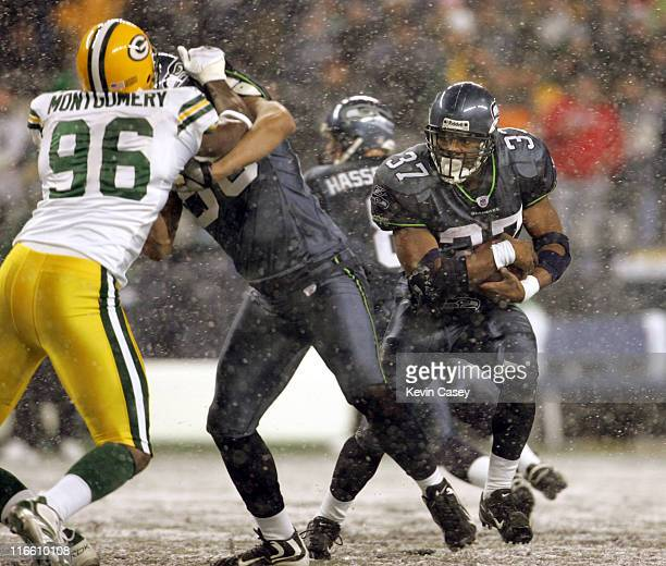 Seahawks Shaun Alexander right runs the ball behind a block by Jerramy Stevens on Green Bay's Michael Montgomery during the first half of the NFL...