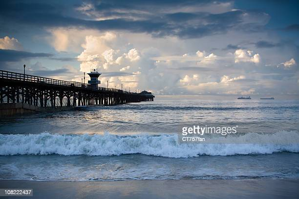 seal beach pier with stormy skies and waves - seal beach stock pictures, royalty-free photos & images