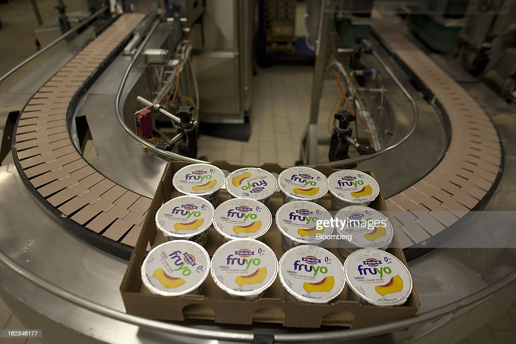 Sealed cartons of Fruyo peach-blended Greek yoghurt pass along a conveyor belt during manufacture at the Fage Dairy Industry SA plant in Athens, Greece, on Thursday, Feb. 21, 2013. An October restructuring that placed Fage International SA's Greek units in a subsidiary called Fage Dairy Industry SA coincided with Coca-Cola Hellenic Bottling SA's plan to flee the epicenter of Europe's debt crisis by moving its main stock listing to London from Athens. Photographer: Kostas Tsironis/Bloomberg via Getty Images