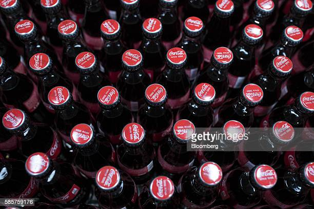 Sealed lids sit on bottles of Coke soft drink on the production line at the CocaCola Co factory in Dongen Netherlands on Thursday Aug 4 2016 CocaCola...