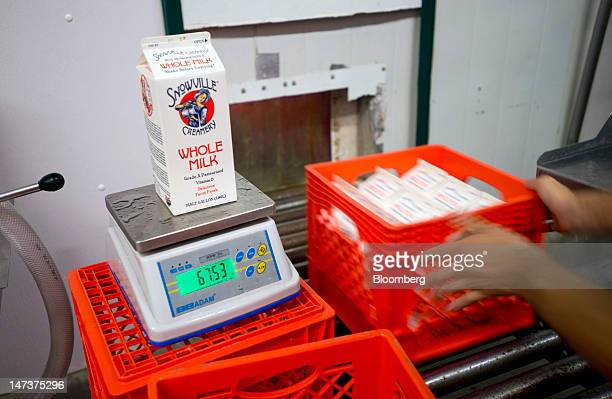 Sealed milk cartons are hand loaded into crates for delivery off the production line at the Snowville Creamery in Pomeroy Ohio US on Thursday June 28...