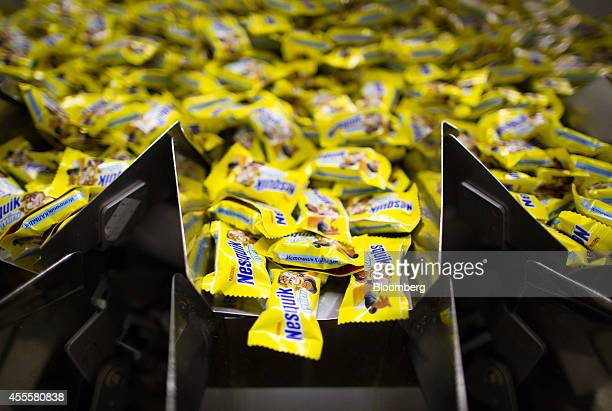 Sealed packets of Nesquik countlines confectionary pass through a processing machine during production at the Rossiya chocolate factory operated by...