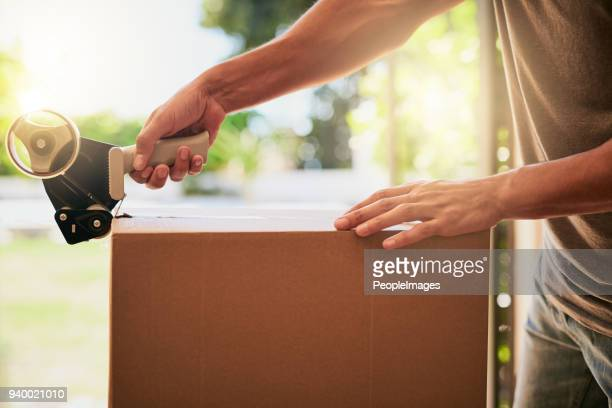 sealing all his belongings for the big move - physical activity stock photos and pictures