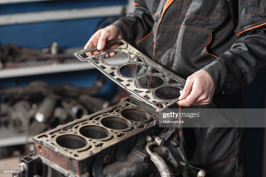 Sealing gasket in hand. The mechanic disassemble block engine vehicle. Engine on a repair stand with piston and connecting rod of automotive technology. Interior of a car repair shop. : Stock Photo