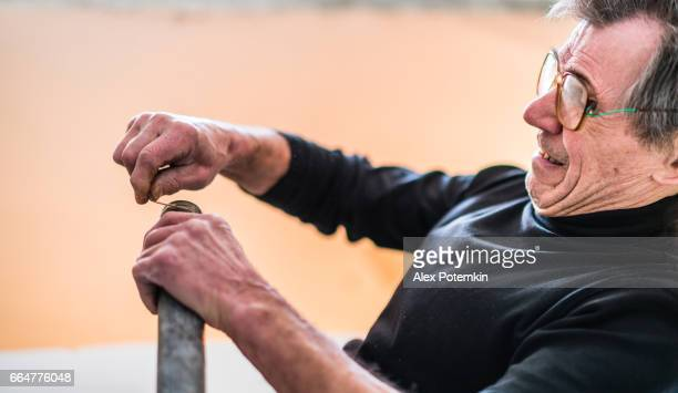 Afdichting van de leidingen. 70-jaar-oud actieve senior man, bouwvakker - loodgieter, die werkt voor home renovatie
