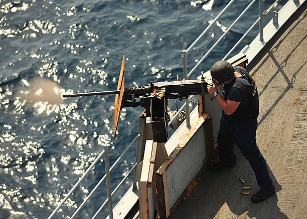 Seaman fires a .50-caliber machine gun aboard USS Gunston Hall.