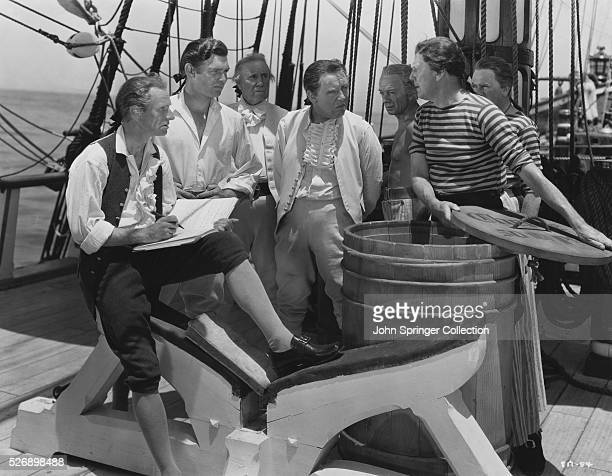 A Seaman holds open a barrel for Captain William Bligh and Fletcher Christian on the deck of the HMS Bounty in the 1935 film Mutiny on the Bounty