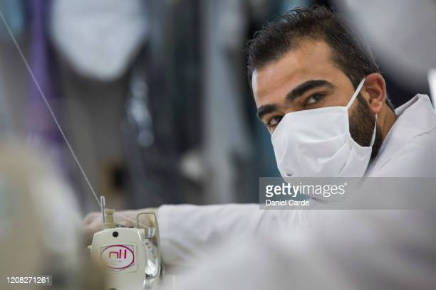 Seamster looks at a colleague while they sew hospital supplies at the Tony Ward Couture fashion house on March 26, 2020 in Beirut, Lebanon. The...