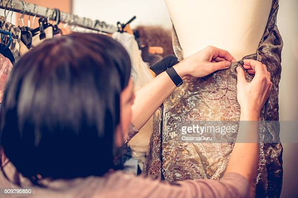Seamstress Adjusting Cloth on Tailor's Dummy