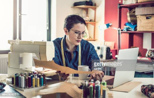 Seamstress Beside a Sewing Machine and Using Laptop