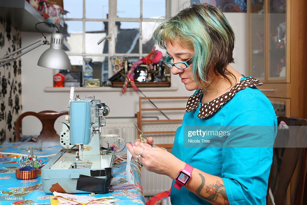 Seamstress cutting fabric working at home. : Stock Photo