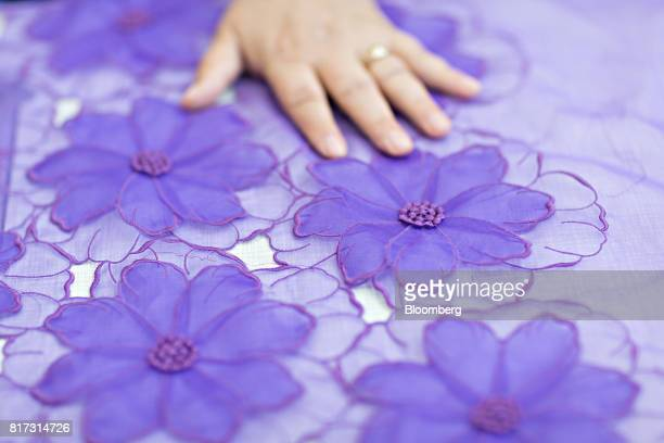 A seamstress inspects embroidered floral detail on a piece of fabric at the Forster Rohner AG textile production workshop in St Gallen Switzerland on...