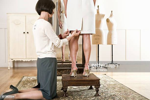 Seamstress looks at dress hem