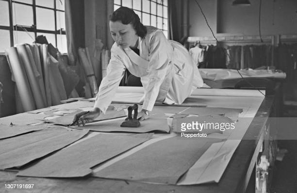 Seamstress marks out patterns on fabric for an outfit, part of a Utility clothing fashion range designed by English fashion designer Norman Hartnell...