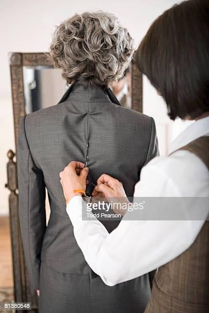 Seamstress pins jacket on woman