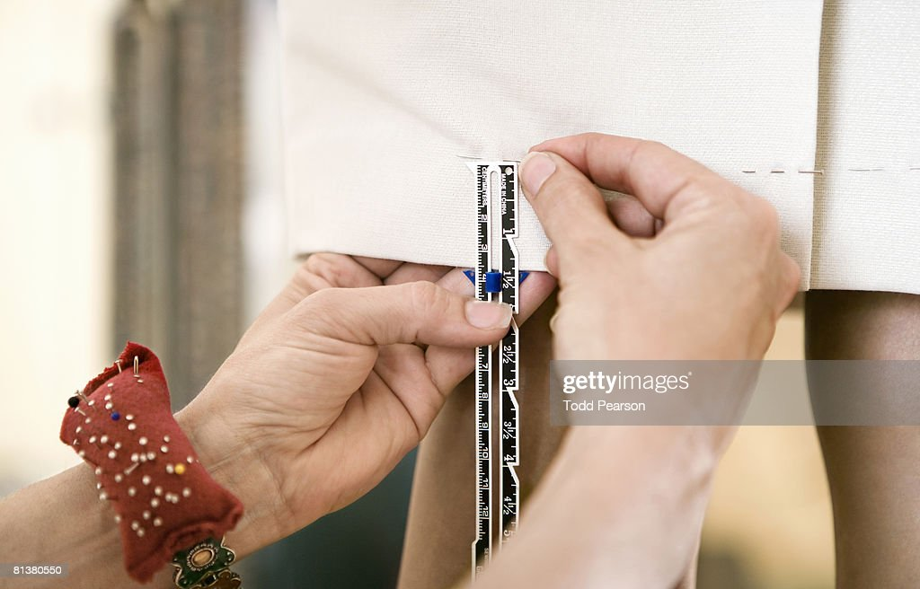 Seamstress puts pins in dress hem : Stock Photo