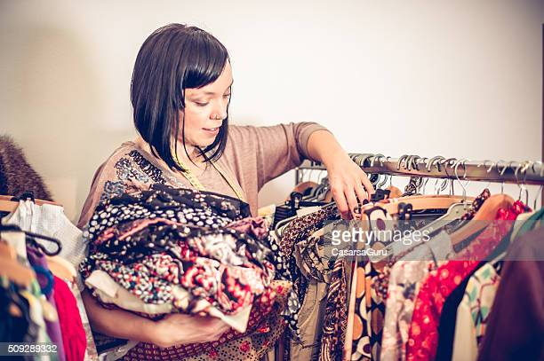 Seamstress Selecting Clothes on Clothing Rack