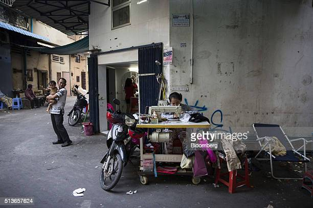 A seamstress sews clothing in an alleyway in Phnom Penh Cambodia on Wednesday March 2 2016 By 2030 more than half of 650 million people in Southeast...