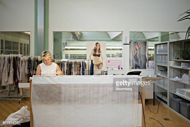 A seamstress sits at an embroidering machine at the Forster Rohner AG textile production workshop in St Gallen Switzerland on Wednesday May 31 2017...