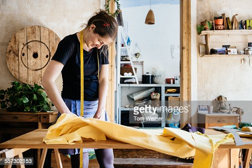Seamstress With Fabric In Her Workshop
