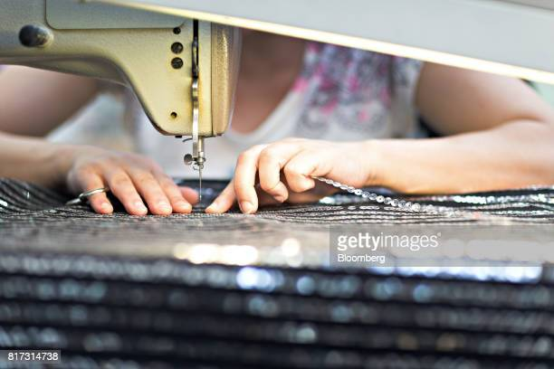 A seamstress works at a sewing machine at the Forster Rohner AG textile production workshop in St Gallen Switzerland on Wednesday May 31 2017 Forster...