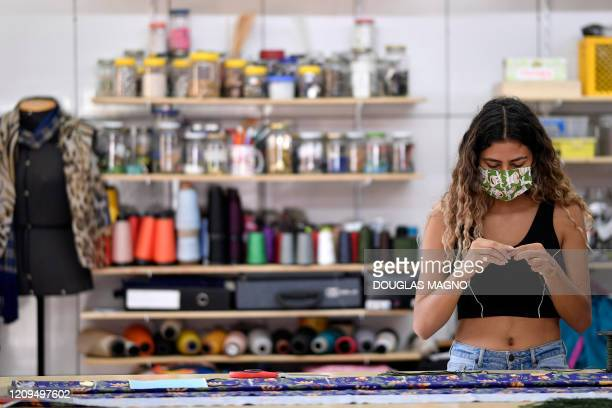 Seamstress works in the making of protective masks against the spread of the new Coronavirus at the Remexe Favelinha atelier of the Vila Novo Sao...