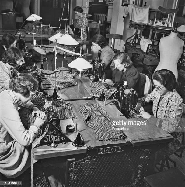 Seamstresses at work on sewing machines to create utility skirt suits to a design by Irish fashion designer Digby Morton at a Bourne and...
