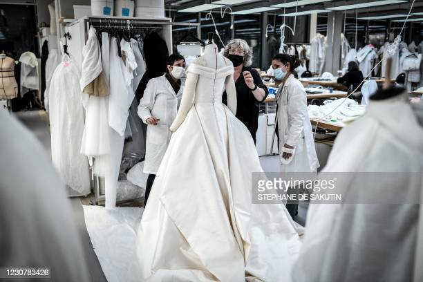 Seamstresses work on a dress at Christian Dior's Haute Couture fashion house workshop in Paris on January 20, 2021. - With no catwalk fashion shows...