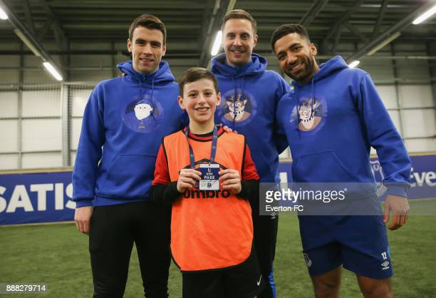 Seamus Coleman of Everton Phil Jagielka of Everton and Aaron Lennon of Everton pose for a photo with a Everton fan during the Coaching Session With a...