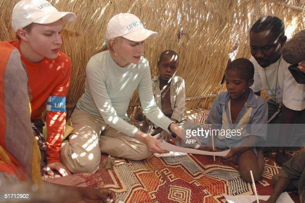 Seamus Farrow and UNICEF Goodwill Ambassador Mia Farrow his mother review drawings made by children in a Safe Play Centre 08 November 2004 in the...
